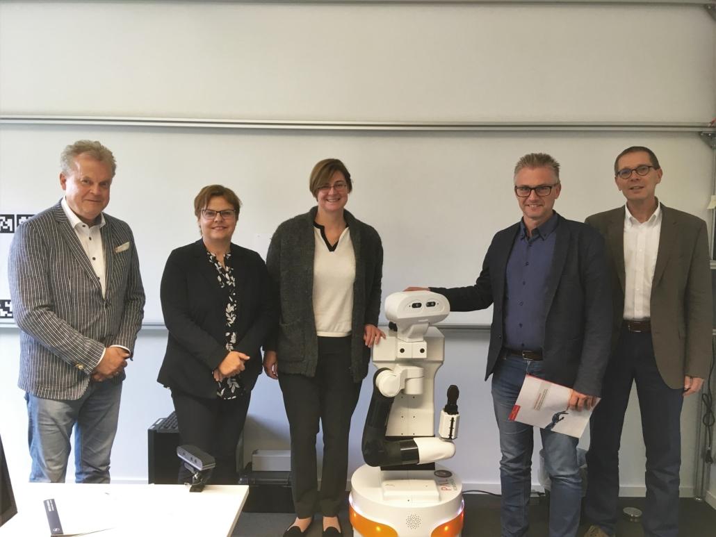 Zu Besuch beim DFKI. V.l.n.r.: Prof. Dr. Wolfgang Lücke, MdL Dr. Silke Lesemann, MdL Dr. Thela Wernstedt, MdL Frank Henning, Prof. Dr. Joachim Hertzberg, zusammen mit dem Experimentierroboter TIAGo des DFKI.